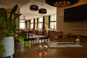 Doorkijk vanuit grand café naar naast met restaurantopstelling